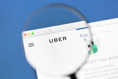 A magnifying glass focusing on Uber logo