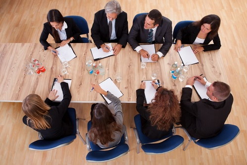 8 formal dressing people with notepads in front of them having a meeting on a wooden desk