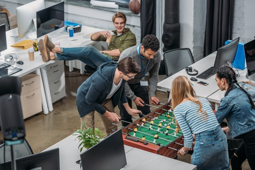 Employees playing foosball in an office environment