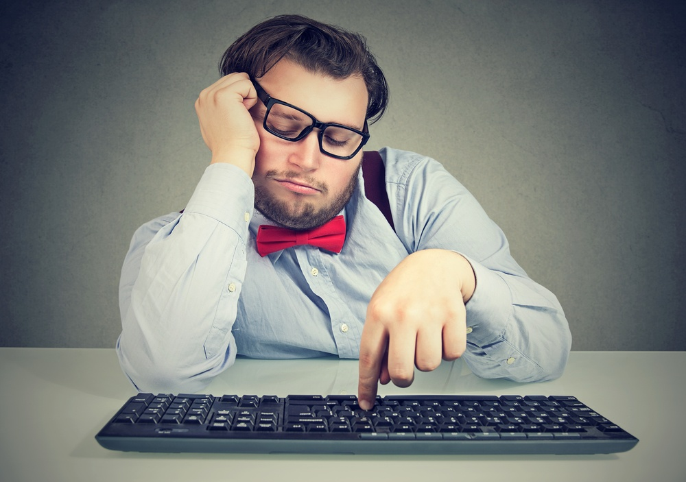 A bored person in front of a computer keyboard